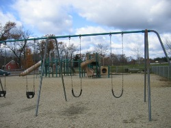 Photo of swingset with 2 toddler and 1 older child swings - on large open sandy area