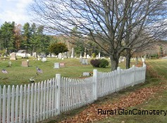 Photo of White picket fence at boundary of cemetery - gravestones in the distance.