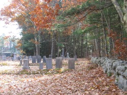 Photo inside of cemetery showing gravestones, with autumn eaves in foregfround - stone fence is along right, running perpendicular to the stones