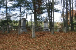 Photo of gravestones in heavily wooded area, with Autumn leaves in foreground