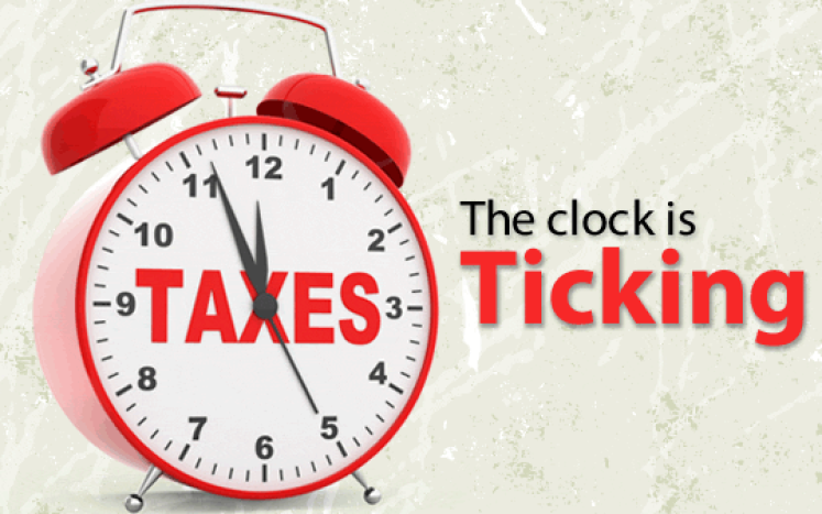 red clock with taxes written on the clock face with writing stating  the clock is ticking