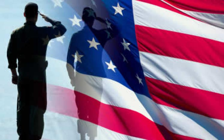 silhouette of a soldier saluting an American Flag