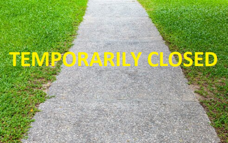walking path with temporarily closed written across in yellow letters
